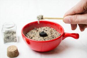 Mit dem Dosierlöffel des Räucherbestecks wird die Räuchermischung auf die Kohle gegeben