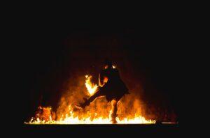 Ein Mann tanzt vor einem Freudenfeuer an Beltane.