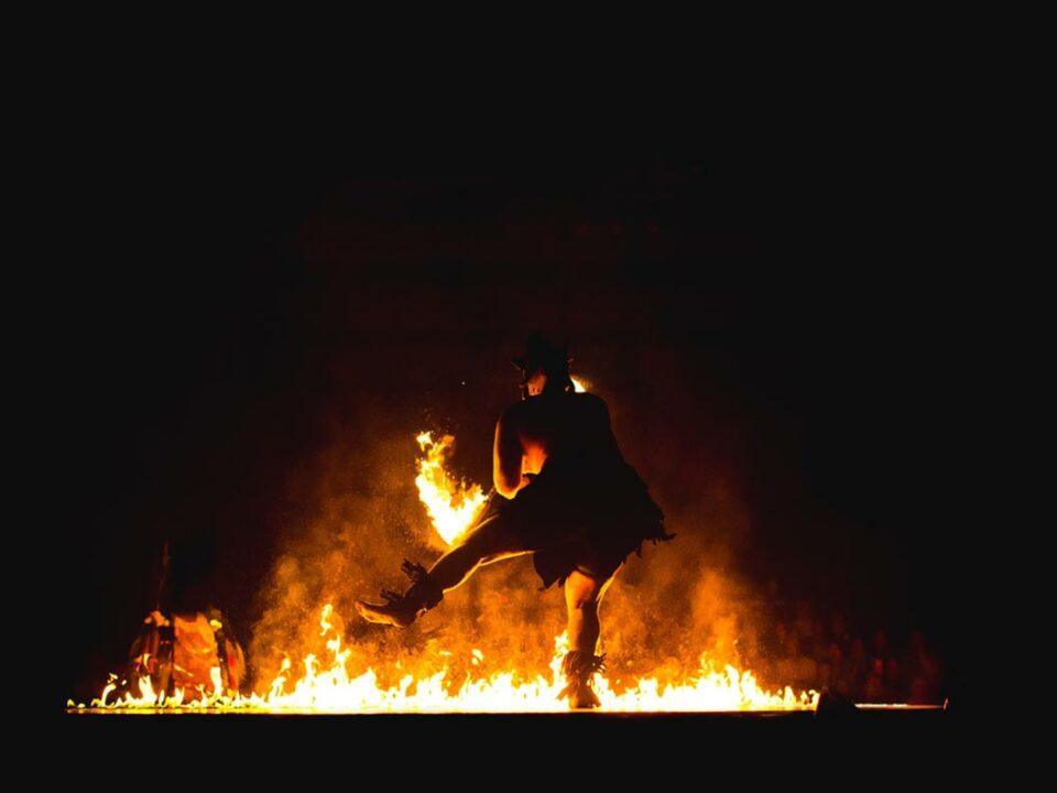 Ein Mann tanzt vor einem Freudenfeuer an Beltane