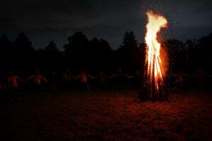 Eine Gruppe Menschen feiert Walpurgisnacht und tanzt um ein Feuer.