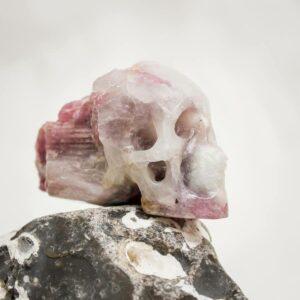 Handgearbeiteter Kristallschädel aus Quarz-Matrixkristall mit rotem Turmalin