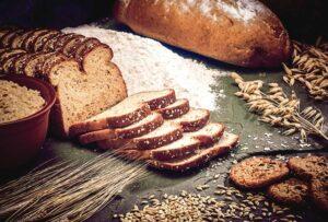 Korn, Mehl und frisch gebackenes Brot auf einer Tischplatte
