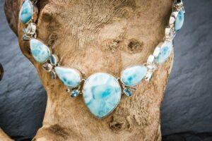 Larimar Collier verziert mit weissem und blauem Topaz arrangiert auf einem Stück Treibholz