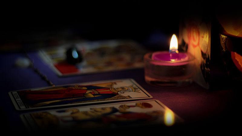 Zwei Tarotkarten aus einer Kartenlegung bei Kerzenschein