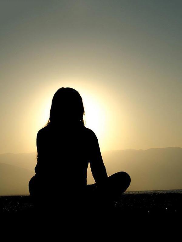 Silhouette einer Frau die im Sonnenuntergang zur Steigerung der Achtsamkeit meditiert.