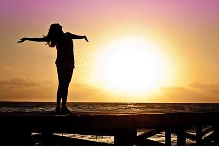 Frau steht auf einem Steg am Ufer, schaut in den Sonnenuntergang und kennt ihren Weg.