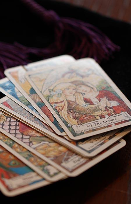 """Ein Stapel tarotkarten liegt auf einem Tisch. Oben auf liegt die Karte """"Die Liebenden""""."""
