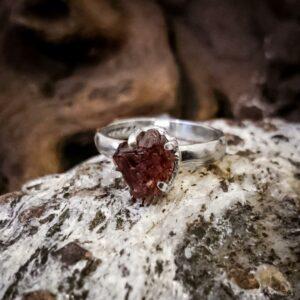 Dieser Ring aus 925er Sterling-Silber setzt einen tiefroten ungeschliffenen Spessartin-Granat durch seine bewusst schlichte Fassung gekonnt in den Mittelpunkt.