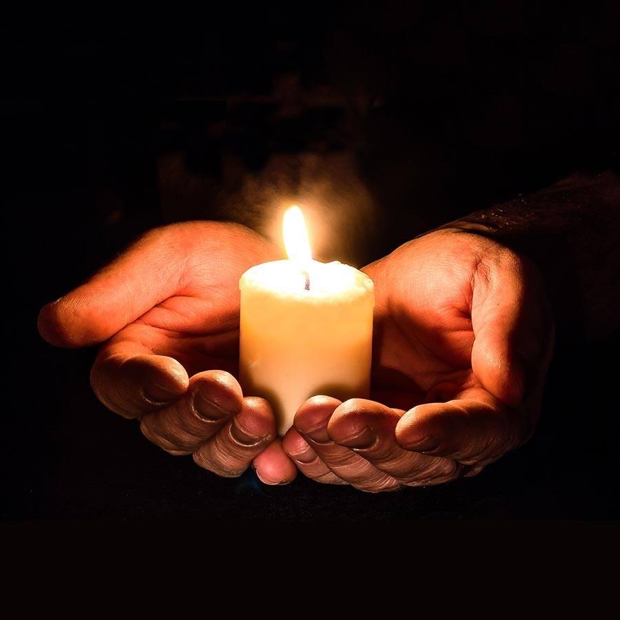 Eine weiße Kerze steht in den Handflächen beider Hände als Symbol für das Weihen von Kerzen zu Imbolc.