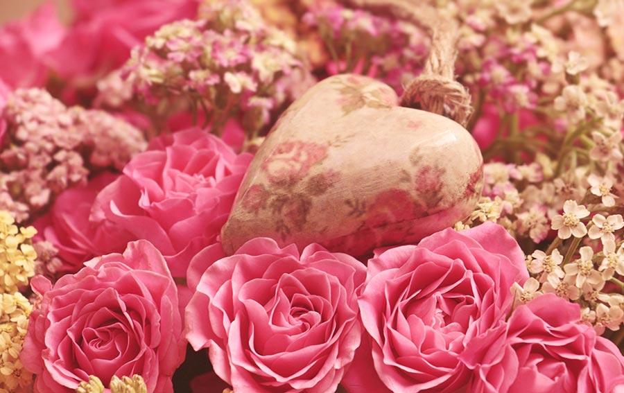 Symbolbild Valentinstag: Ein Herz liegt auf einem Bett aus rosa Rosen.