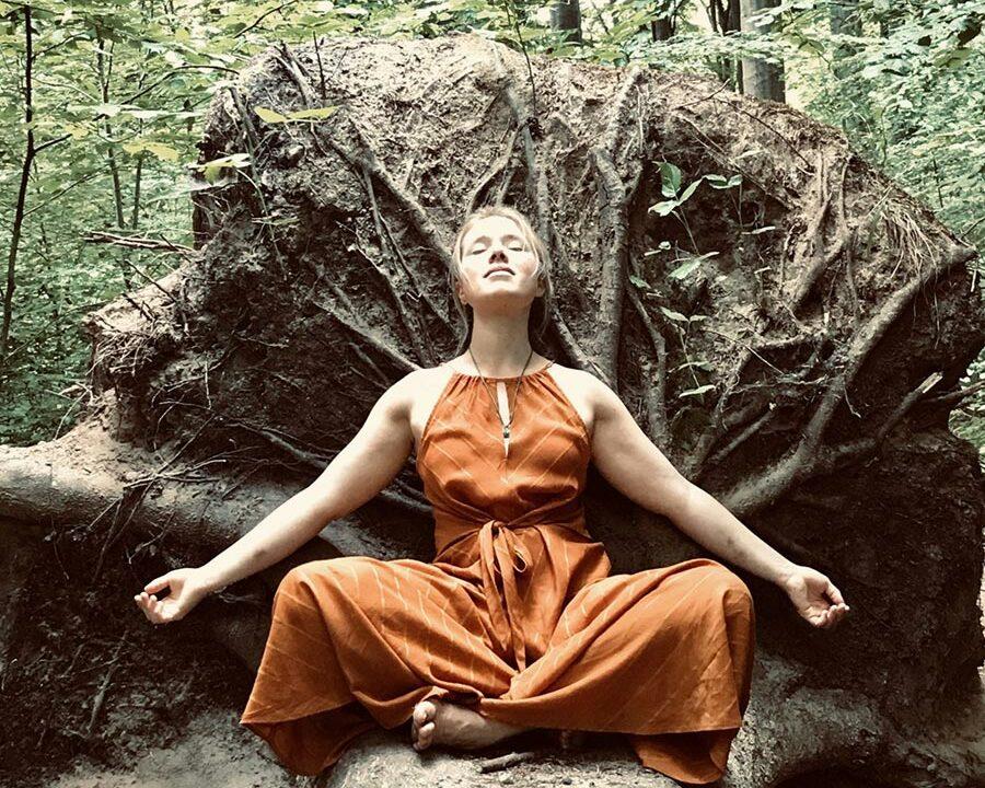 Swanje Vanessa Sagebiel meditiert im Wald an einer Baumwurzel