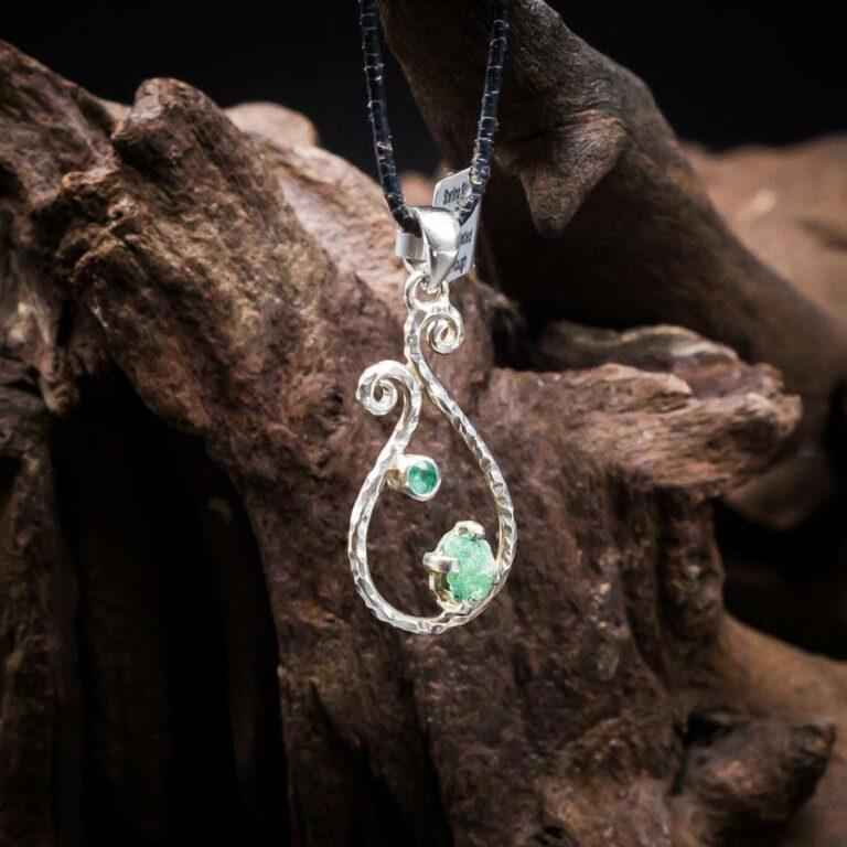 Anhänger mit einem Smaragd Rohkristall und einem Smaragd facettiert, verspielt gefasst in 925er Sterling-Silber